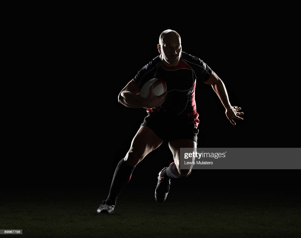 Rugby player with ball side stepping