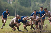 Rugby players covered with mud, tackling opponent