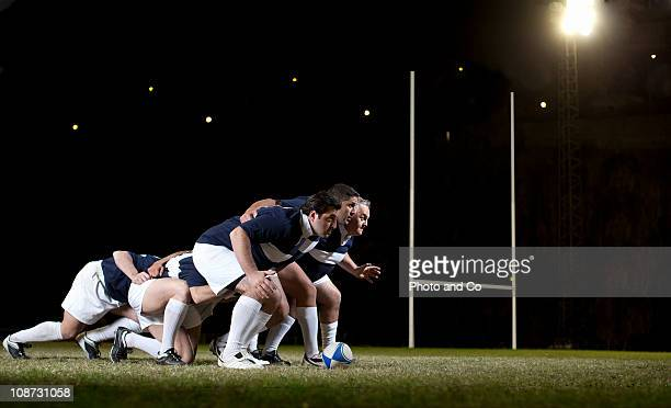 Rugby players in scrum on pitch