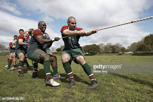 Rugby players playing tug of war on field