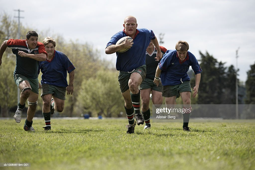 Rugby players running with ball on sports field