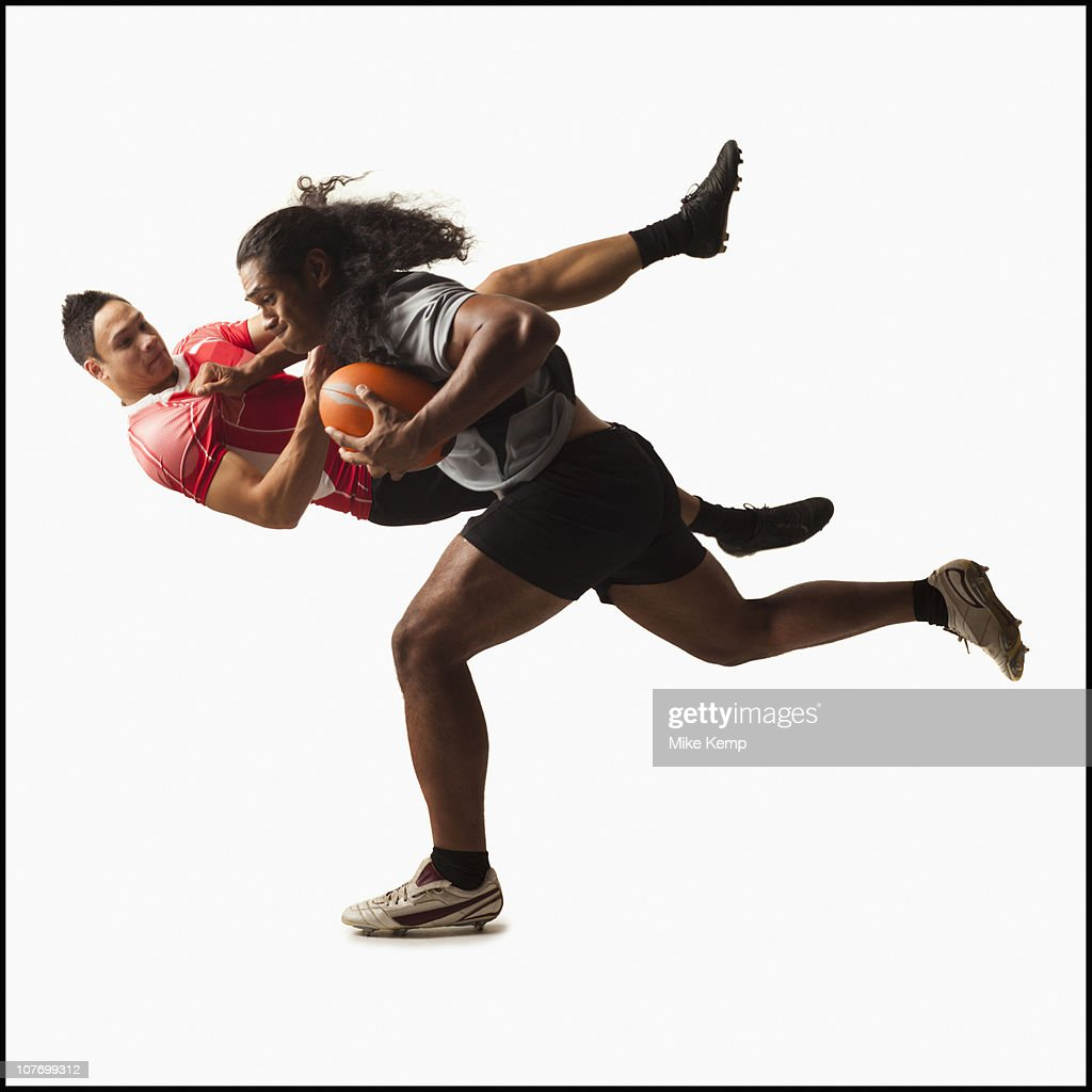 Rugby players tackling for ball