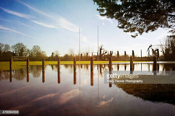 Rugby post reflections in sportsground flooding.
