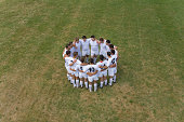 Rugby team standing in circle on pitch, elevated view