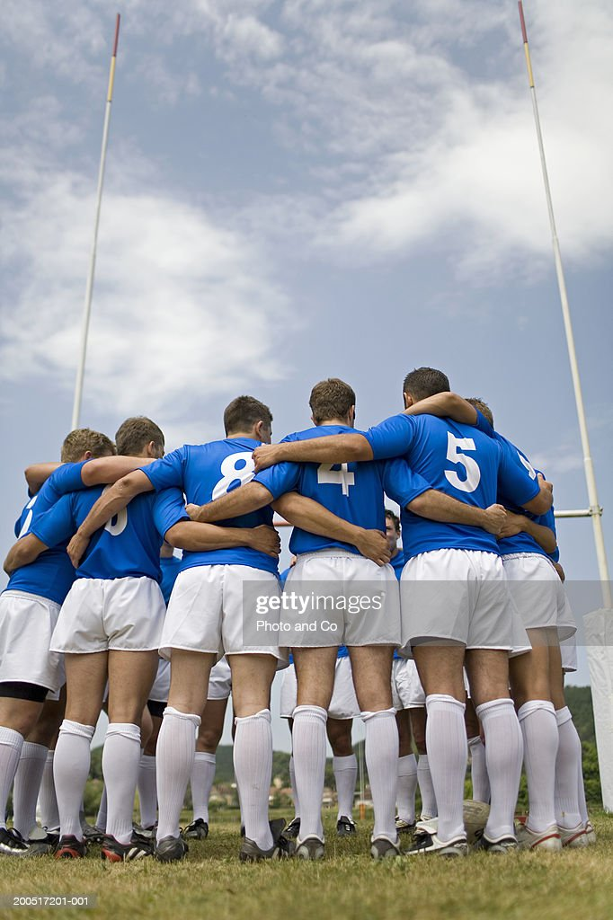 Rugby team standing with arms locked in circle on pitch : Stock Photo