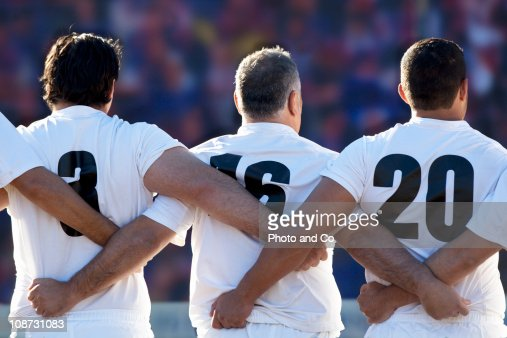 Rugby team standing with arms locked, rear view : Stock Photo