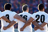 Rugby team standing with arms locked, rear view