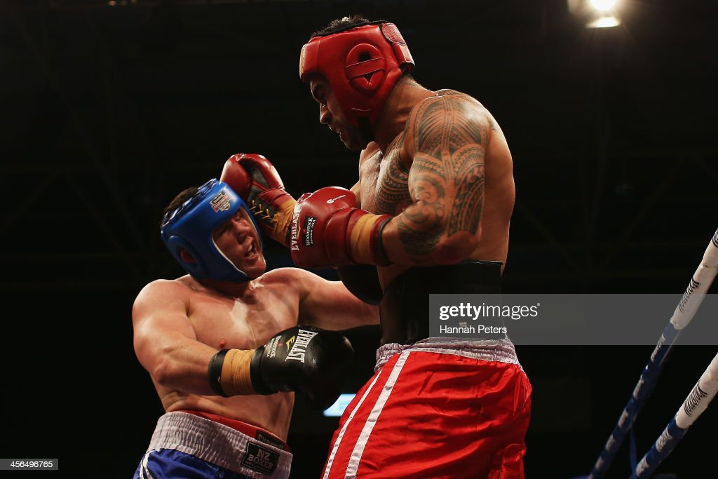 Rugby union player <a gi-track='captionPersonalityLinkClicked' href=/galleries/search?phrase=Liam+Messam&family=editorial&specificpeople=601526 ng-click='$event.stopPropagation()'>Liam Messam</a> fights rugby league player Paul Gallon during 'Fight for Life' at The Trusts Stadium on December 14, 2013 in Auckland, New Zealand.