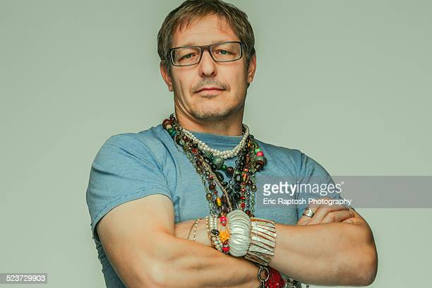 Rugged looking man sporting women's jewelry