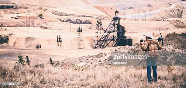 Robuste Mann steht neben rock quarry mit pickaxe an den Schultern