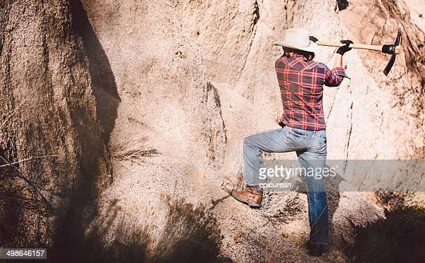 Rugged Man uses pickaxe against rock face