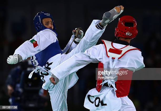 Rui Braganca of Portugal kicks Oscar Luis Munoz Oviedo of Colombia during the Taekwondo Men's 58kg Round One contest on Day 11 of the Rio 2016...
