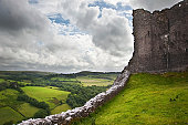 Beautiful image of medieval castle ruins in landscape with moody sky background