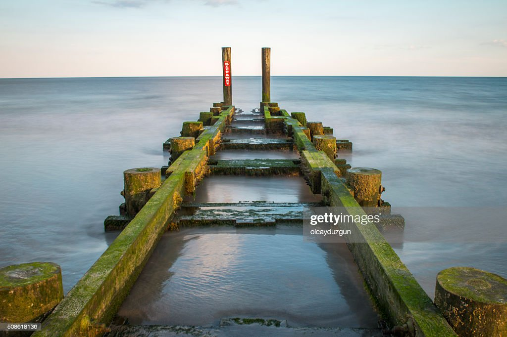 Ruined pier through ocean : Stock Photo