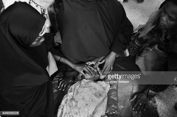 Rukayo center and her sister Lu left close the eyes and mouth of Rukayo's severely malnourished son in preparation for his impending death at Banadir...