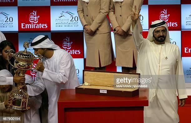 Ruler of Dubai sheikh Mohamed Bin Rashid alMaktoum celebrates as his son Crown Prince Sheikh Hamdan receives the Dubai World Race trophy after his...