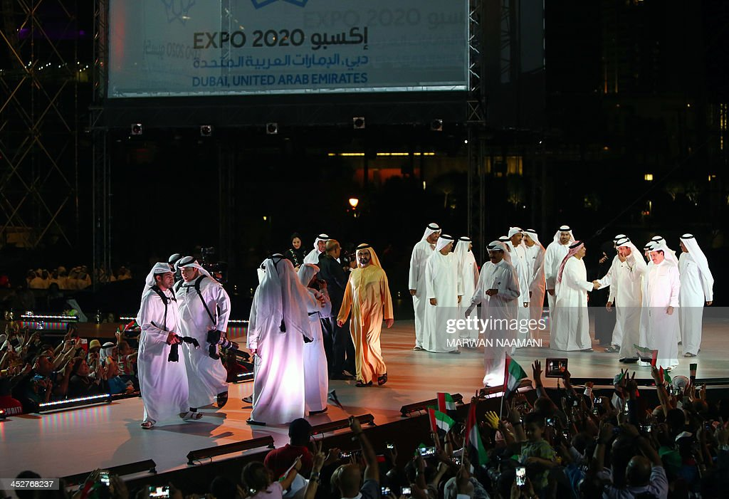 Ruler of Dubai Sheikh Mohammed Bin Rashid al-Maktoum (C) and officials arrive to take part in celebrations near Dubai's Burj Khalifa, the world's tallest tower, on December 1, 2013, marking the United Arab Emirates national day and the victory for Dubai to host the 2020 World Expo. A jubilant Dubai hopes that hosting the world's five-yearly trade fair in 2020 will draw new investment to an economy still recovering from a debt crisis that required a bailout by Abu Dhabi PHOTO