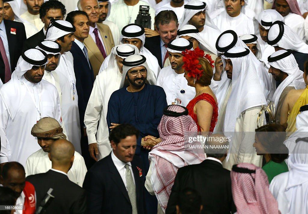 Ruler of Dubai Sheikh Mohammed Bin Rashid al-Maktoum (C), flashes a smile, as he waits for Jockey Silvester De Sousa who lead Sajjhaa, owned by Godolphin stables, to win in the Dubai Duty Free part of the Dubai World Cup meet, the world's richest race, at Meydan race track in Dubai March 30, 2013. AFP PHOTO/MARWAN NAAMANI