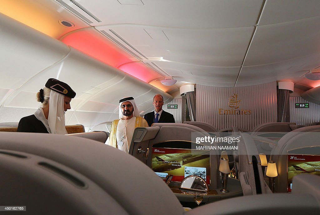 Ruler of Dubai Sheikh Mohammed Bin Rashid al-Maktoum (C), takes a tour of the Emirates A380 airliner, alongside Tom Enders (R), chief executive of the European aerospace giant EADs, during the opening ceremony of the Dubai Airshow on November 17, 2013.