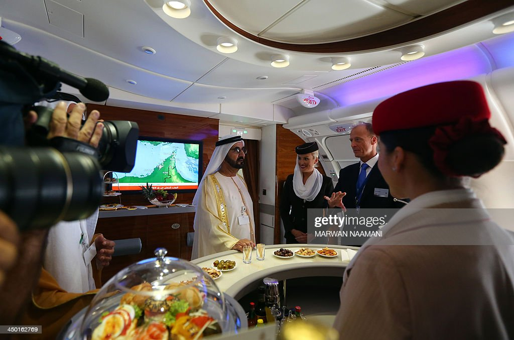 Ruler of Dubai Sheikh Mohammed Bin Rashid al-Maktoum (C), takes a tour of the Emirates A380 airliner, alongside Tom Enders (2nd-R), chief executive of the European aerospace giant EADs, during the opening ceremony of the Dubai Airshow on November 17, 2013.