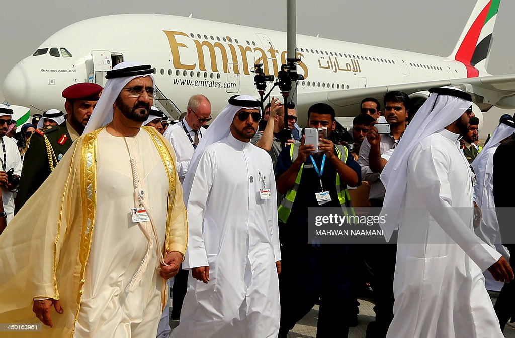 Ruler of Dubai Sheikh Mohammed Bin Rashid al-Maktoum (L) walks past an Emirates Airline's Airbus A380 as he attends the opening ceremony of the Dubai Airshow on November 17, 2013. AFP PHOTO/MARWAN NAAMANI