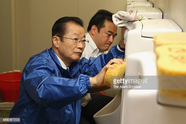 Ruling Liberal Democratic Party lawmaker and former chief cabinet secretary Takeo Kawamura clean an urinal of a toilet in the diet building on...