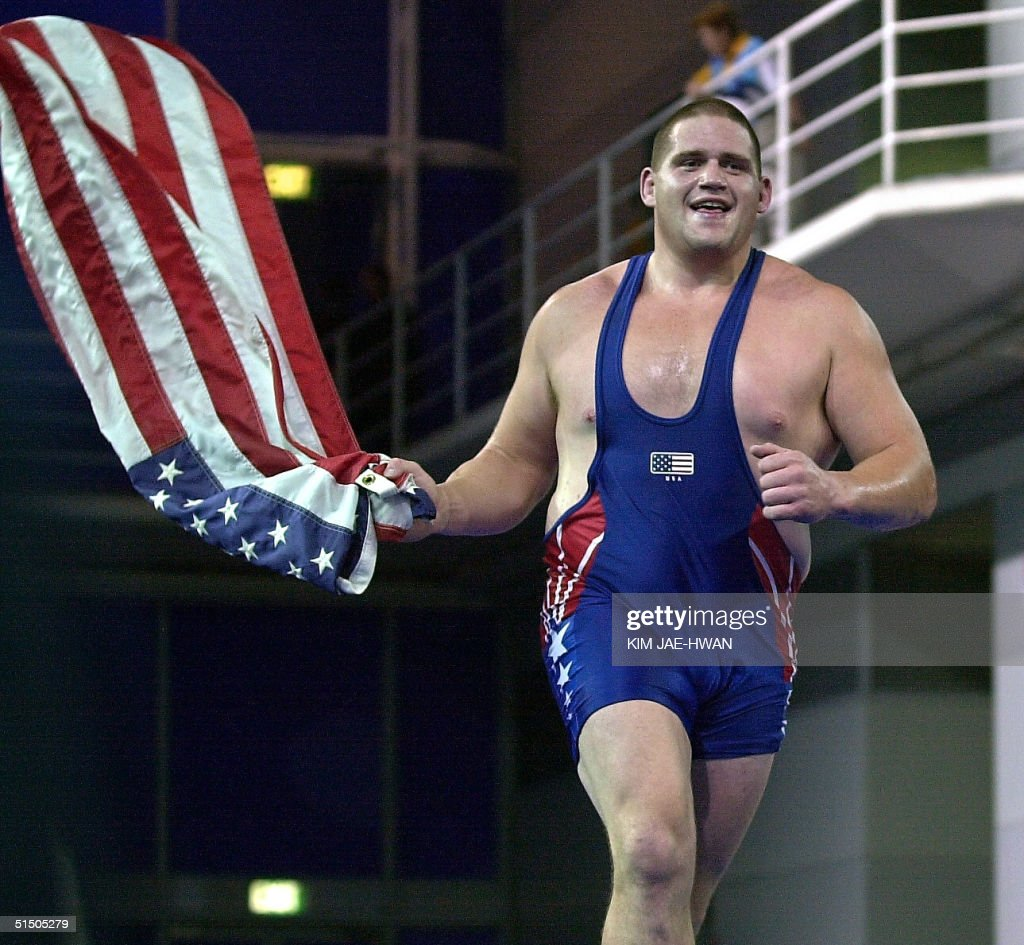 Rulon Gardner of the USA waves the Stars Stripes following his upset victory over Russia's Kareline Alexandre in the final of the men's 130kg...