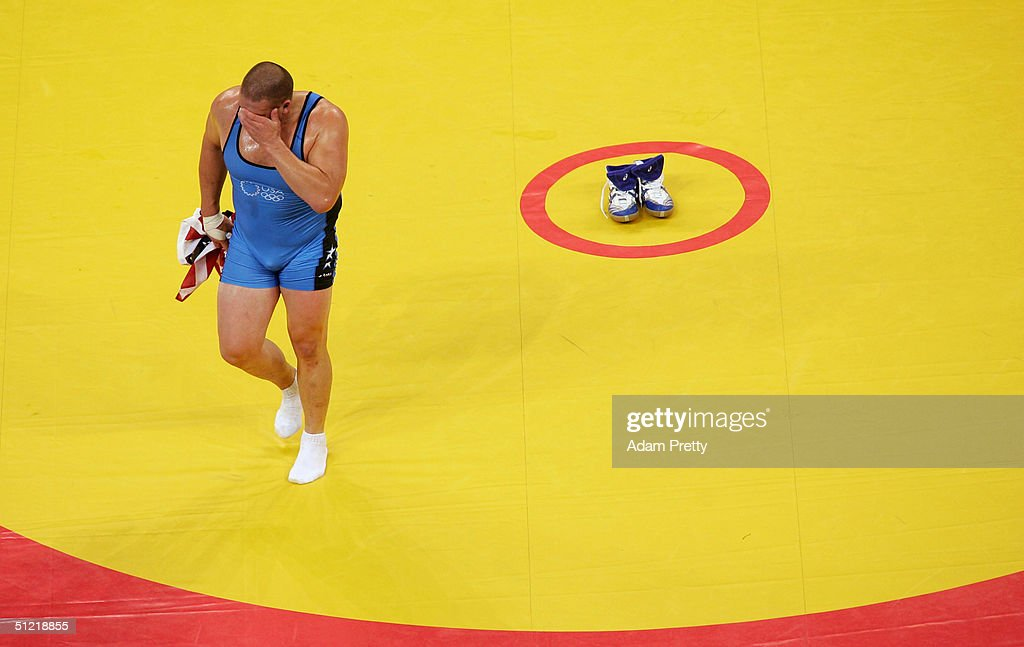 Rulon Gardner of the USA wipes his face as he walks off the mat leaving his shoes behind to signify his retirement after winning the bronze medal...
