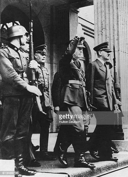 Rumanian premier Ion Antonescu on a visit to Munich in July 1941 gives the Nazi salute as he leaves a building with Adolf Hitler Six days later...