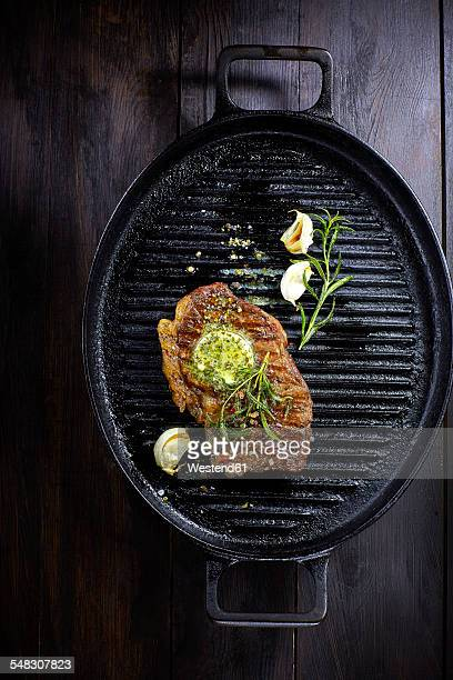 Rump steak with herbed butter, rosmary and garlic in frying pan