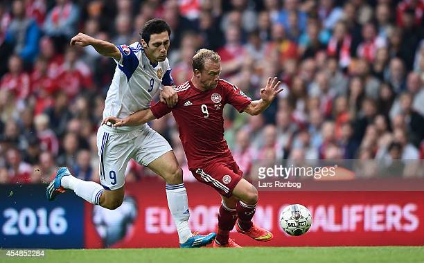Rumyan Hovsepyan of Armenia and Michael KrohnDehli of Denmark compete for the ball during the UEFA 2016 Group I Qualifier between Denmark and Armenia...