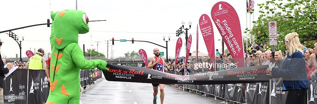 Runner and 4 time winner of mens-marathon; Scott Wietecha celebrate as he crosses the finish-line in the St. Jude Rock 'n' Roll Nashville Marathon/Half Marathon and 5k where more than 34,000 participants weathered the rain during the 17th running on April 30, 2016 in Nashville, Tennessee.