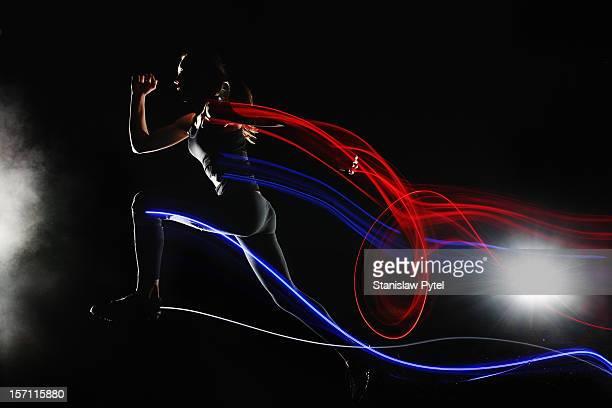 Runner at night leaving streaks of light