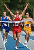 Runner breaking through finish line