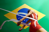 Runner Breaking through the finishing line tape over Brazilian flag