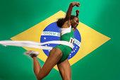 Runner Breaking through the finishing line tape over Brazilian flag