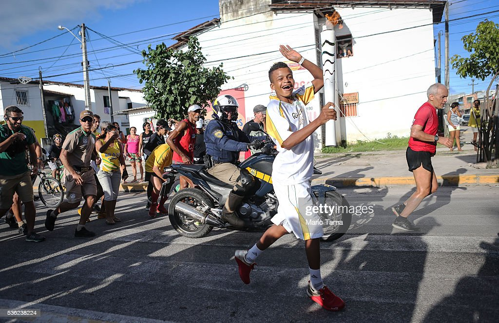 A runner carries the Olympic flame as security and onlookers follow on May 31, 2016 in Recife, Brazil. The Olympic flame will pass through 329 cities from all states from the north to the south of Brazil, before arriving in Rio de Janeiro on August 5, for the lighting of the cauldron for the Rio 2016 Olympic Games. The games will be held amidst an economic and political crisis in the country.