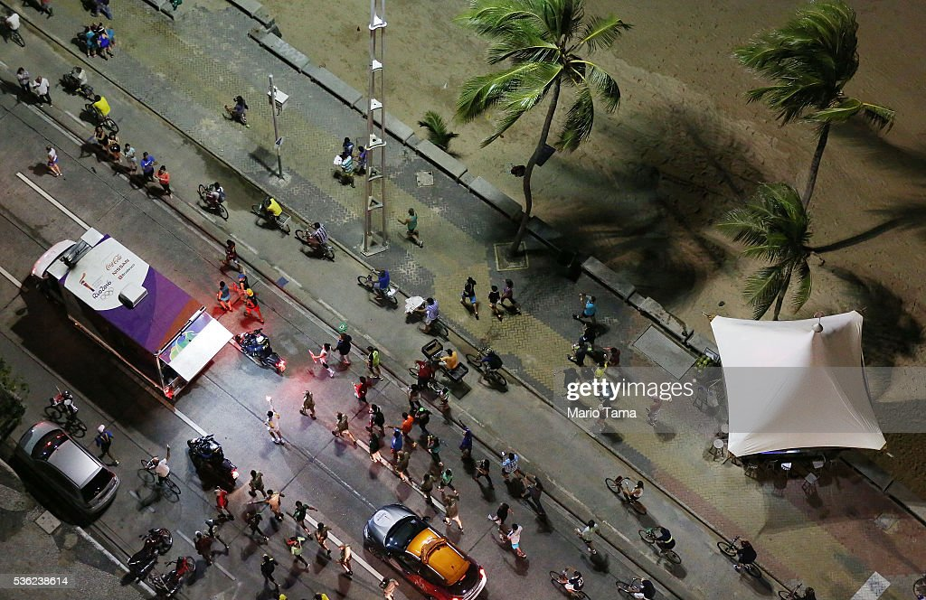 A runner carries the Olympic flame as security and onlookers follow along the beach on May 31, 2016 in Recife, Brazil. The Olympic flame will pass through 329 cities from all states from the north to the south of Brazil, before arriving in Rio de Janeiro on August 5, for the lighting of the cauldron for the Rio 2016 Olympic Games. The games will be held amidst an economic and political crisis in the country.