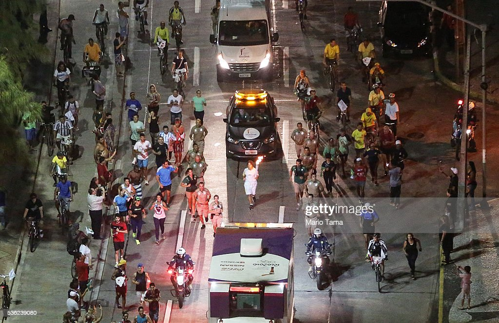 A runner carries the Olympic torch as security and onlookers follow on May 31, 2016 in Recife, Brazil. The Olympic flame will pass through 329 cities from all states from the north to the south of Brazil, before arriving in Rio de Janeiro on August 5, for the lighting of the cauldron for the Rio 2016 Olympic Games. The games will be held amidst an economic and political crisis in the country.