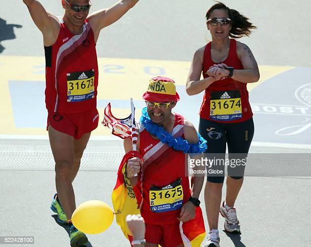 A runner carrying an American flag crosses the finish line of the 120th Boston Marathon on Monday April 18 2016