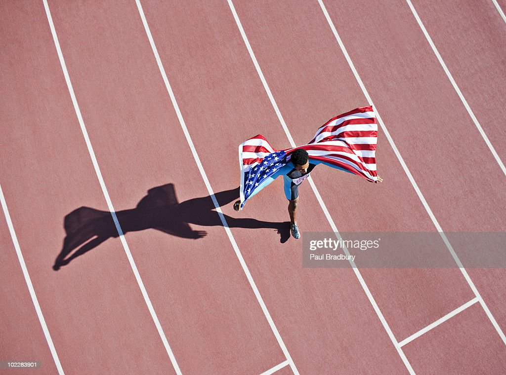 Runner celebrating on track with American flag : Stock Photo