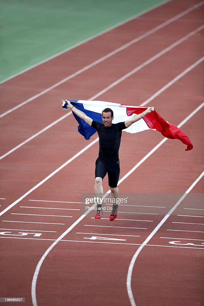 Runner celebrating with French flag on track : Stock Photo