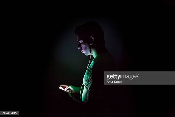 Runner checking his smartphone music at night.