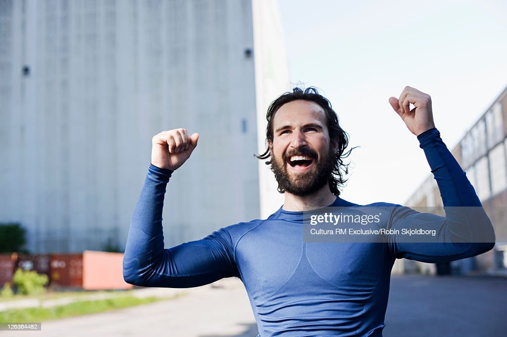 Runner cheering in industrial area : Stock Photo