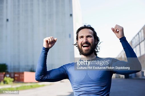 Runner cheering in industrial area : Bildbanksbilder