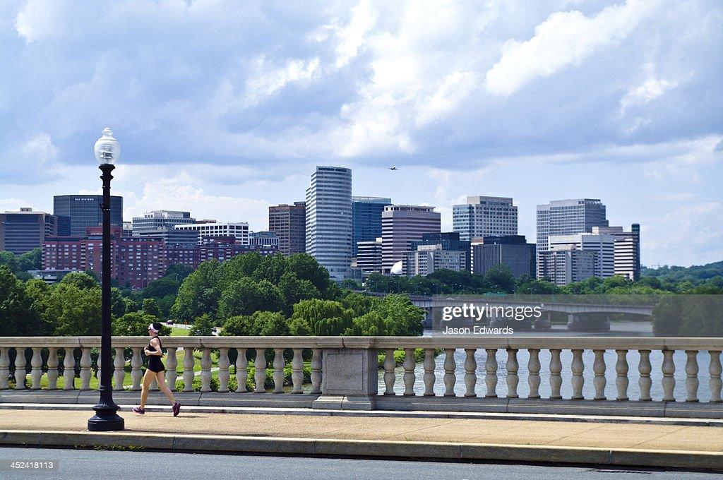A runner crosses the Arlington Memorial Bridge over the Potomac River.