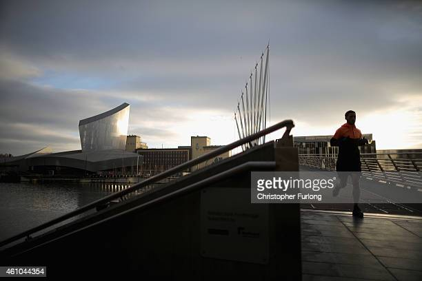 A runner crosses the bridge at Media City in Salford Quays which is home to the BBC ITV television studios and also houses many media production...