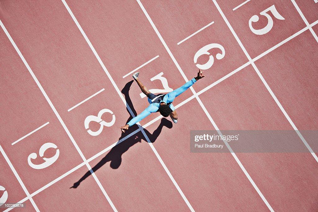 Runner crossing finishing line on track : Stock Photo