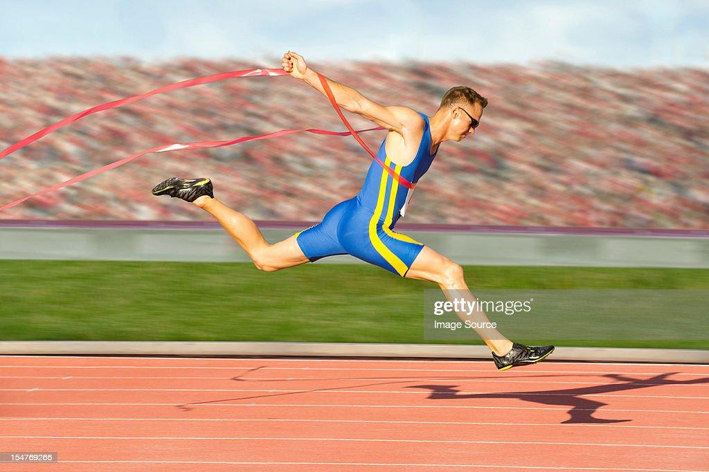 Runner crossing the finish line : Stock Photo