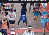 A runner does a hand stand as they cross the finish line on The Mall during the Virgin Money London Marathon on April 24 2016 in London England